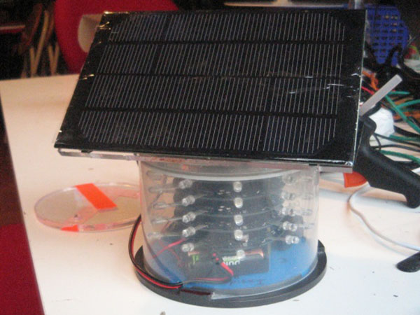 Round plastic enclosure with a number of LEDs visible inside, on top of a battery pack. A solar panel site on top of the round enclosure.