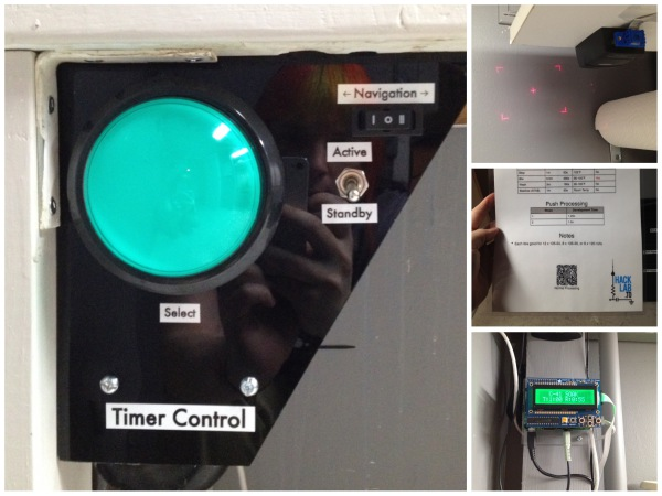 On the left, a control panel with one large green button and a number of smaller switches. In the upper right, a barcode scanner making a laser crosshair on the wall. In the upper middle, a paper sheet with a 2D barcode at the bottom. In the lower right, a green LCD display that says C-41 Soak and the time remaining.